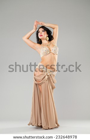 Portrait of the young sexy woman in long arabic skirt on gray background