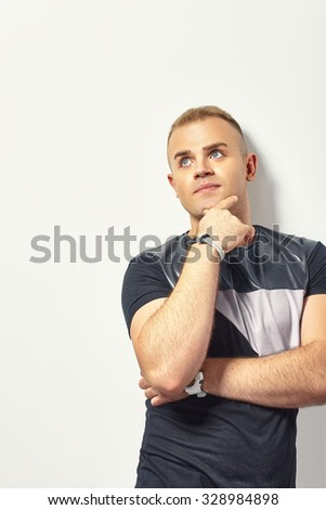 Portrait of the young thinking man looks up with hand near face  - stock photo