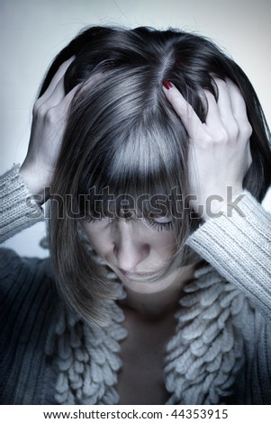 Portrait of the young woman with headache squeezing her head with hands, head down - stock photo