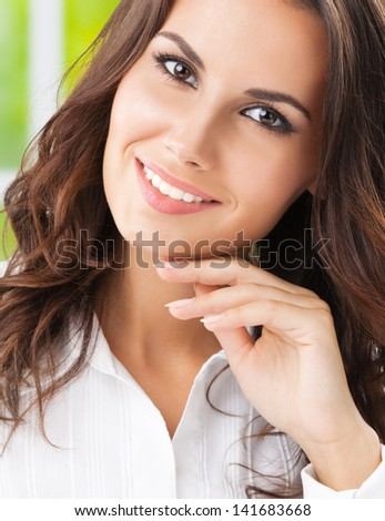 Portrait of thinking cheerful business woman at office
