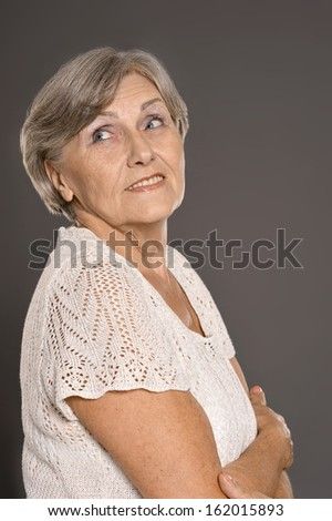 Portrait of thinking elderly woman on grey background