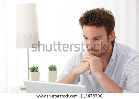 Portrait of thinking man using laptop computer at home, copyspace. - stock photo