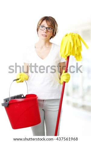 Portrait of thinking middle age woman holding in her hand mop and mopping bucket.