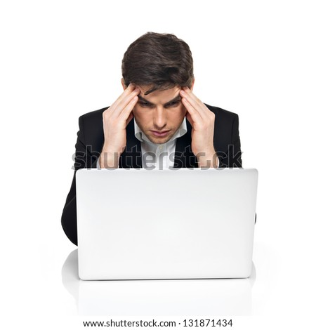 Portrait of thinking office worker with laptop having stress sitting on the table,  isolated on white.