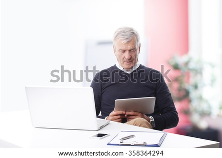 Portrait of thinking old businessman reading on digital tablet while sitting at office in front of laptop.  - stock photo