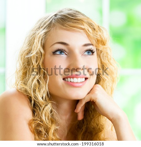 Portrait of thinking young beautiful blond woman, at home - stock photo