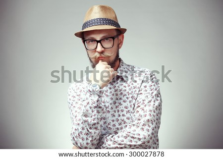 Portrait of thinking young hipster in a hat isolated on grey background