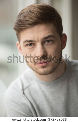 Portrait of thinking young man near glass window. Reflection from model on the glass.