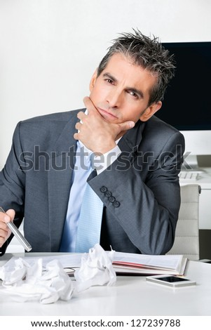 Portrait of thoughtful businessman sitting at desk in office - stock photo