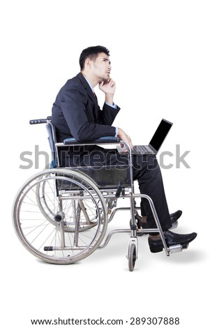 Portrait of thoughtful disabled businessman with laptop, sitting on wheelchair while imagine something - stock photo