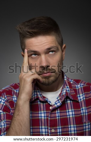 Portrait of thoughtful handsome man on dark grey. Man in maroon plaid shirt dreaming about serious things in his life. - stock photo