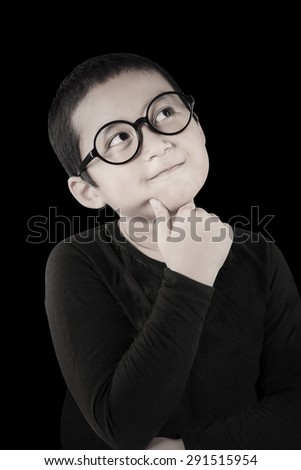 Portrait of thoughtful little boy with casual clothes and wearing a round glasses, shot with black background - stock photo