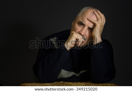 Portrait of  thoughtful mature man in low key - stock photo