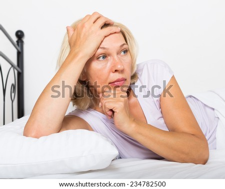 Portrait of thoughtful mature woman   in bedroom - stock photo