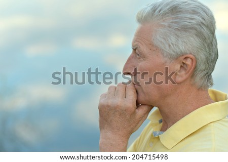 Portrait of thoughtful old man on sky background