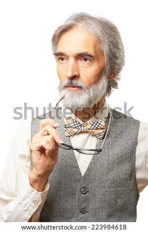Portrait of thoughtful senior caucasian man with a gray beard and bowtie holding glasses isolated on white background - stock photo