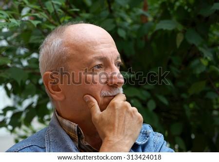 Portrait of thoughtful senior man outdoors - stock photo