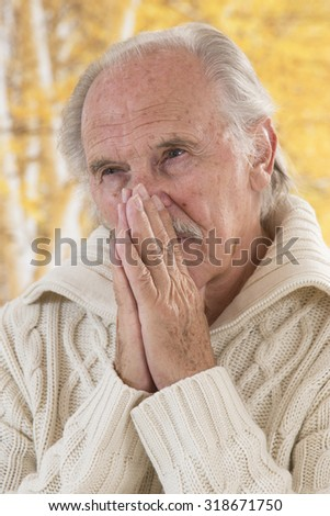 portrait of thoughtful  senior man outdoors - stock photo