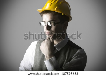 Portrait of thoughtful smart young engineer with helmet against grey background