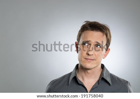 Portrait Of Thoughtful Young Man Looking Away Over Grey Background - stock photo