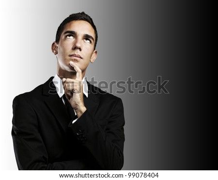 portrait of thoughtful young man wearing suit against a black background - stock photo