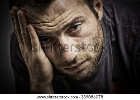 Portrait of thoughtful young man with hand on forehead, looking at camera. - stock photo