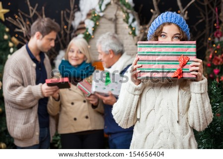Portrait of thoughtful young woman holding Christmas present with family standing in background at store - stock photo