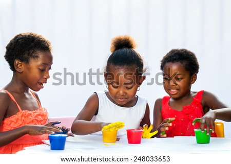 Portrait of three African kids painting with hands.Isolated against light background.