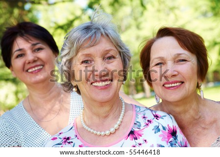 Portrait of three aged women looking at camera with smiles - stock photo