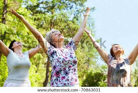 Portrait of three aged women with her arms raised and enjoy
