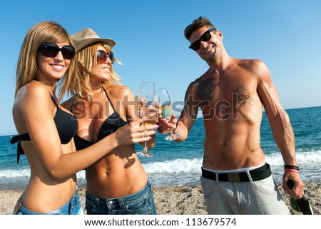 Portrait of three attractive friends making a champagne toast on the beach. - stock photo