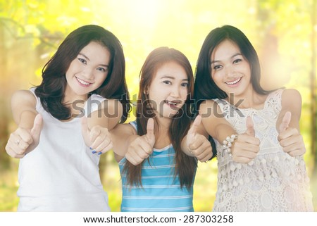 Portrait of three beautiful teenage girls enjoy summer holiday and showing thumbs up on the camera - stock photo
