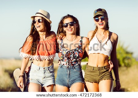 Portrait of three beautiful young women enjoying summer on road trip.