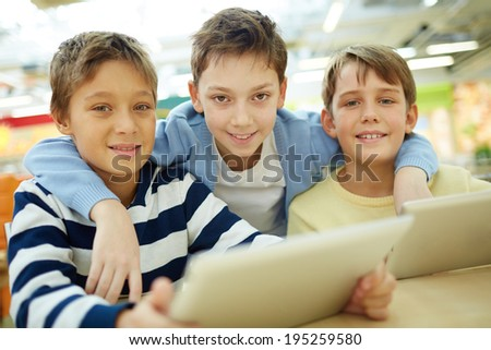 Portrait of three boys with touchpads sitting in cafe - stock photo
