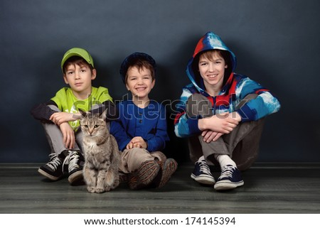 Portrait of three brothers on blue background, studio - stock photo