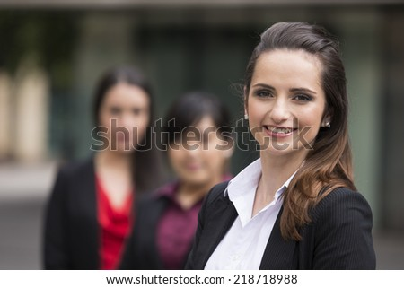 Portrait of three business women. Focus is on caucasian woman at the front. Interracial group of business women.