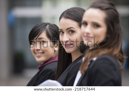 Portrait of three business women. Shallow depth-of-field/focus used to highlight the asian woman at the end of row.   - stock photo