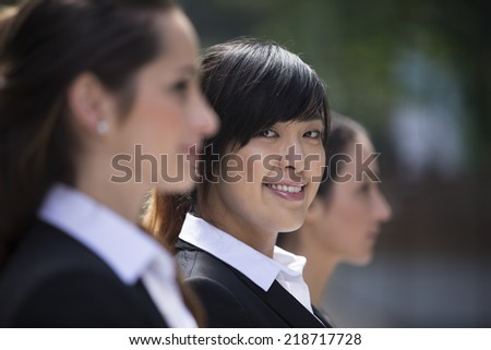 Portrait of three business women. Shallow depth-of-field/focus used to highlight the Asian woman in the middle. Interracial group of business women. - stock photo