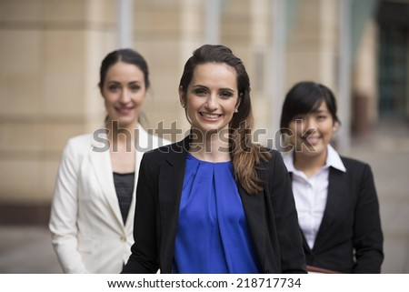 Portrait of three business women. Shallow depth-of-field, focus used to highlight the woman in the middle. Interracial group of business women.