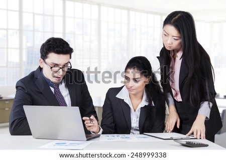 Portrait of three businesspeople are busy working in the office and make a business plan - stock photo