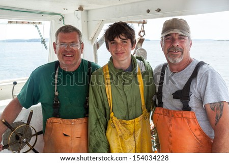 Portrait of three caucasian lobster-men in boat, Maine, USA - stock photo