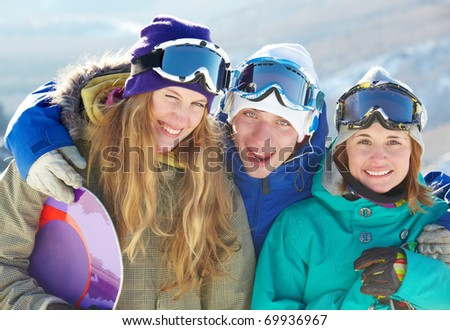 Portrait of three cheerful friends in ski goggles looking at camera and smiling