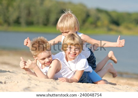 Portrait of three children playing on the beach - stock photo