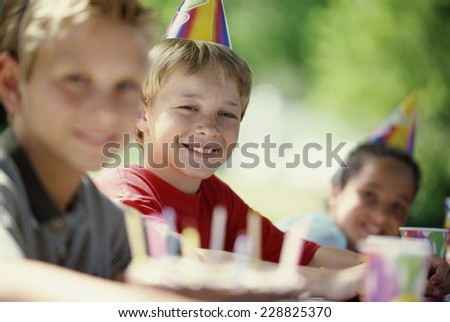 Portrait of three children posing at a birthday party - stock photo