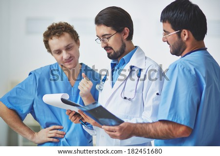 Portrait of three clinicians in uniform discussing document - stock photo