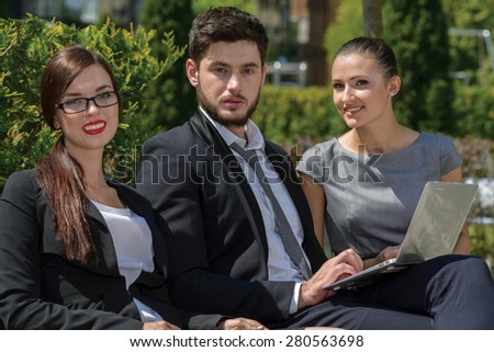 Portrait of three  confident and motivated business partners. All are sitting and discussing business details of current projects. All are wearing formal suits. Outdoor business concept - stock photo
