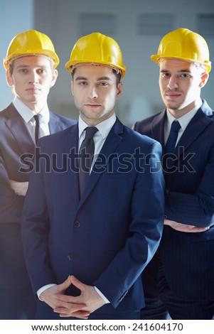 Portrait of three confident men in hardhats - stock photo