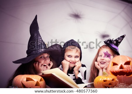 Portrait of three cute children in Halloween costumes reading a book