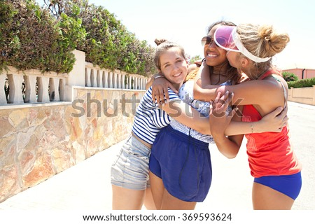 Portrait of three diverse friends, caucasian and african american black teenagers, hugging and kissing in a colorful suburban street on a sunny day, house exterior. Adolescents friendship outdoors. - stock photo