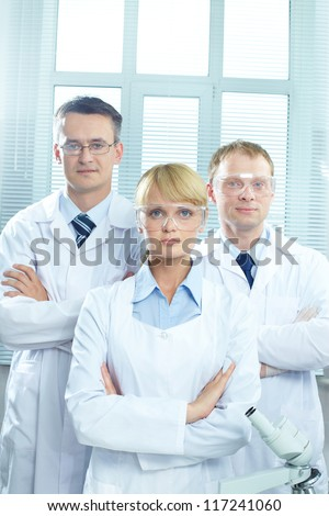 Portrait of three doctors in uniform looking at camera - stock photo